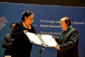 La rectora Sara Ladrón de Guevara y el guitarrista en el momento de la condecoración
