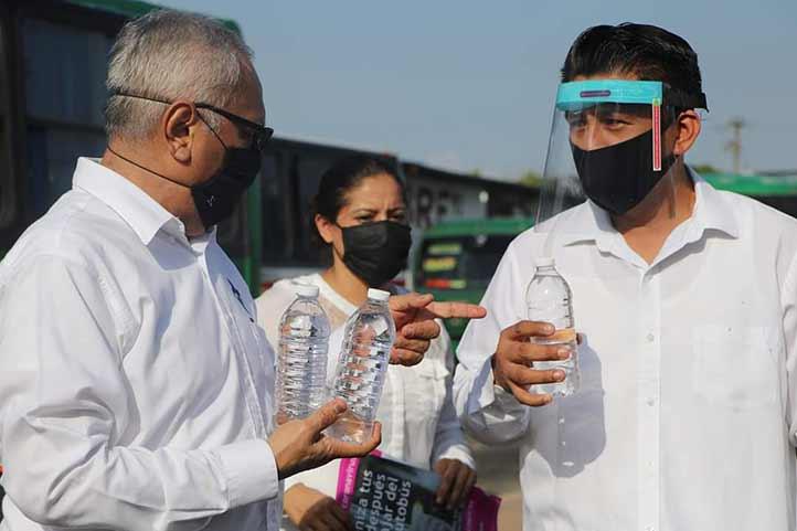 Gabriel Zárate Flores entregando la solución desinfectante a conductores de transporte público